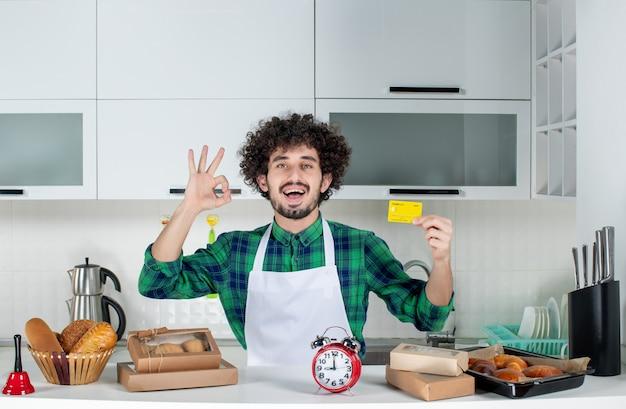 Vista frontale del giovane sorridente in piedi dietro il tavolo vari pasticcini su di esso e in possesso di carta di credito e facendo un gesto ok nella cucina bianca