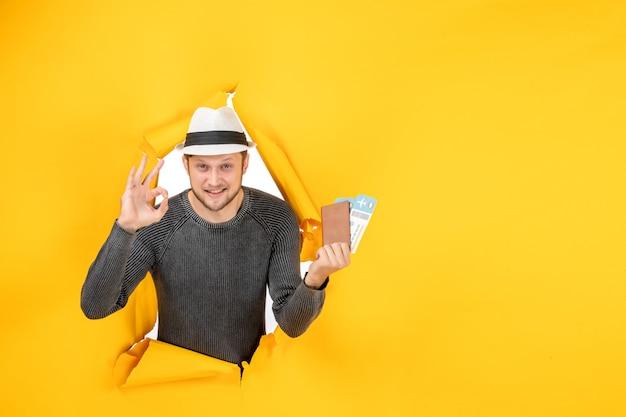 Vista frontale di un giovane sorridente con un cappello che tiene in mano un passaporto straniero con un biglietto e fa il gesto degli occhiali in un muro strappato sul giallo