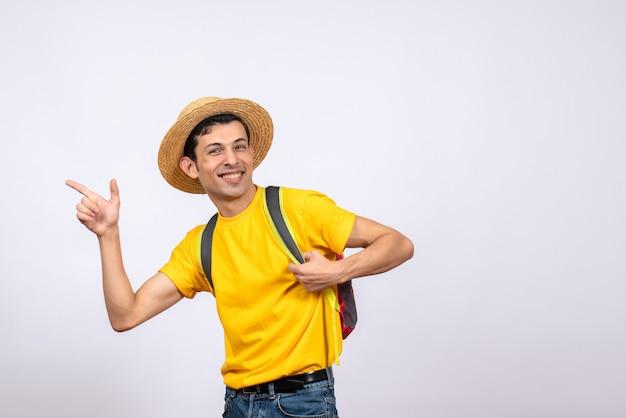 Вид спереди улыбающегося молодого человека с красным рюкзаком и желтой футболкой, указывающим на что-то