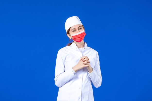 Front view smiling young nurse in medical suit with red protective mask on blue