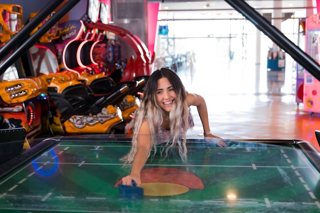 Front view smilling woman playing air hockey