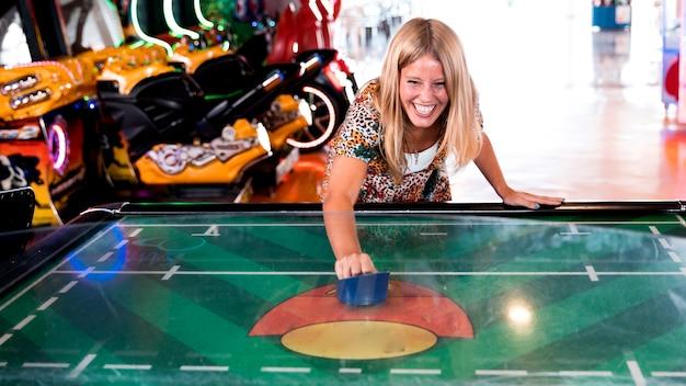 Вид спереди улыбающаяся женщина играет в воздушный хоккей