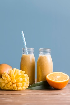 Front view smoothie bottles with mango and orange