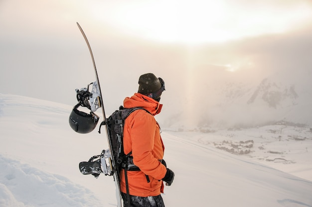 Front view of snowboarder looking on mountain peaks