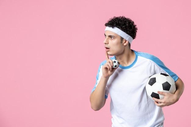 Вид спереди футболист в спортивной одежде с мячом