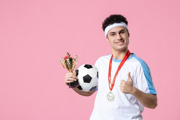 Вид спереди футболист в спортивной одежде с золотым кубком и медалью