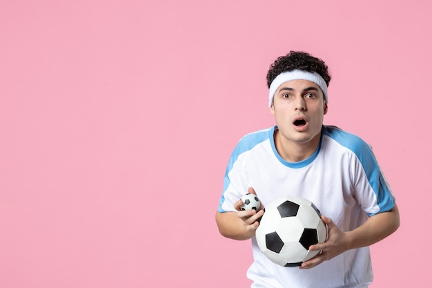 Front view soccer player in sport clothes with ball
