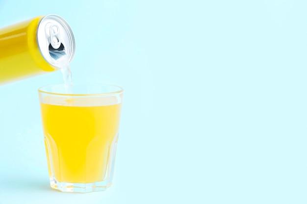 Vista frontale della bevanda analcolica che versa in vetro dalla latta