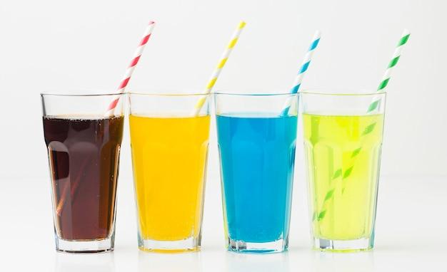 Vista frontale di bibite analcoliche in bicchieri con cannucce