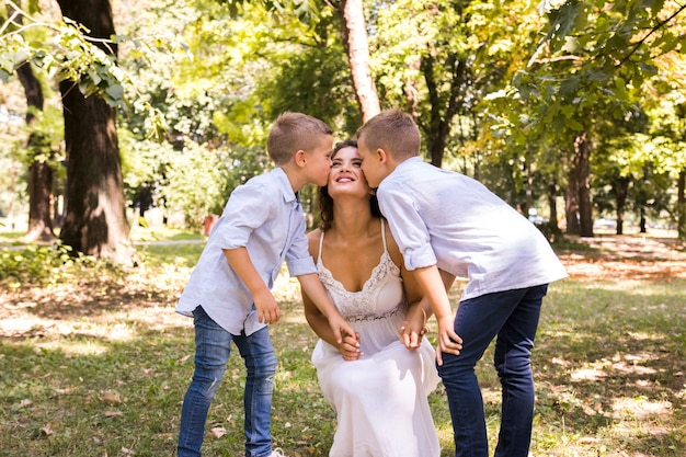 Front view sons kissing their mother