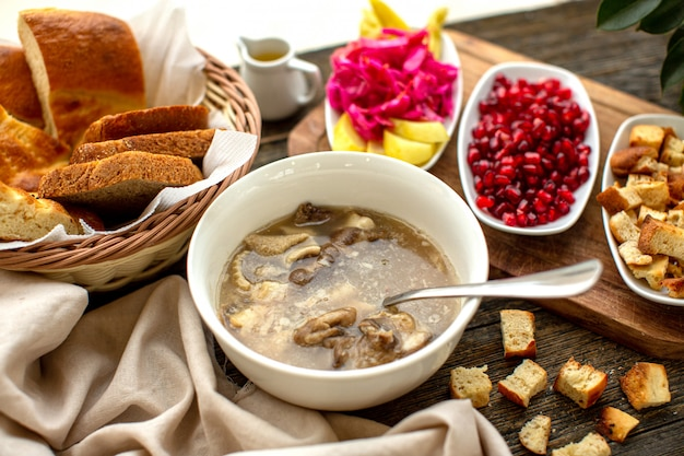 A front view soup meat tasty along with peeled out pomegranate dried bread slices on the brown wooden rustic surface