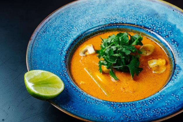 キノコとプレートにライムのスライスとハーブの正面スープ