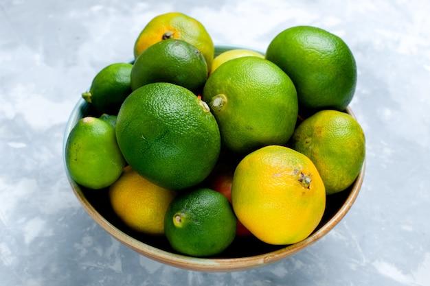 Вид спереди кислые свежие мандарины с лимонами на светло-белом столе цитрусовые экзотические тропические фрукты витамин кислый