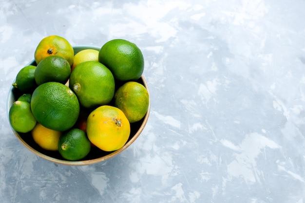 Вид спереди кислые свежие мандарины с лимонами на светлой белой поверхности цитрусовые экзотические тропические фрукты витамин кислый