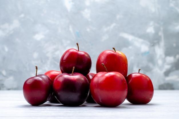 Una vista frontale aspro prugne rosso mellow e succoso sullo sfondo bianco frutta fresca colore aspro