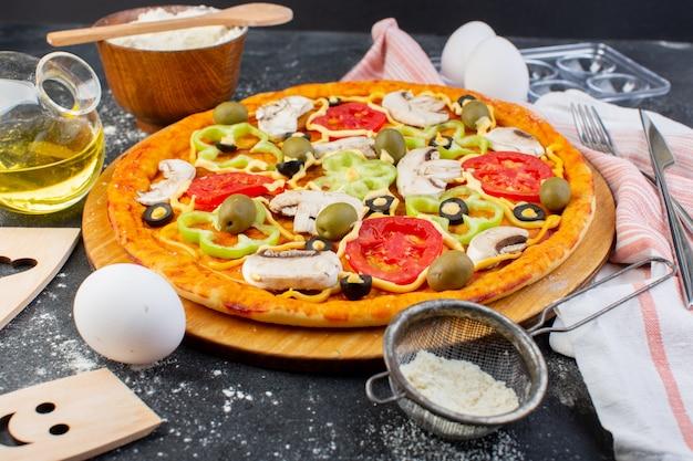 Pizza di funghi piccanti vista frontale con pomodori rossi peperoni olive tutte affettate all'interno con olio e farina su grigio