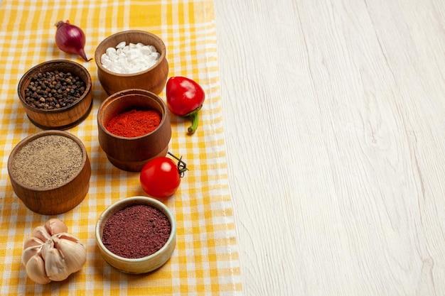 白い机の上の野菜とスパイシーな調味料の正面スパイシーでエッジの効いた熟した食事