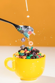 Front view spoon and bowl with cereals and milk