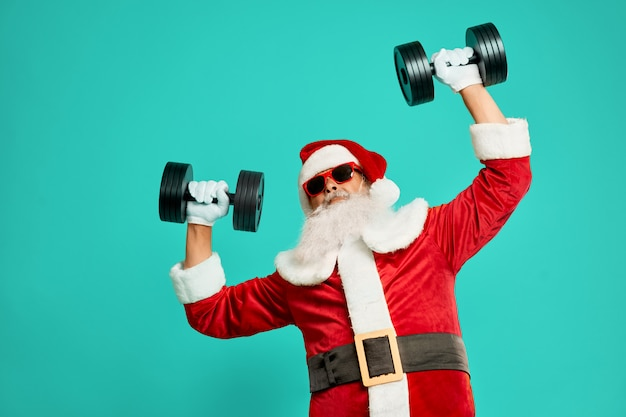 Front view of sportive santa claus holding dumbbels. isolated crop of funny senior man in christmas costume and sunglasses posing