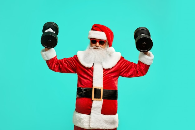 Front view of sportive santa claus holding dumbbels. isolated portrait of funny senior man in christmas costume and sunglasses posing