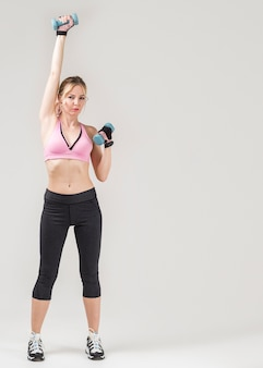 Front view of sporty woman exercising with weights