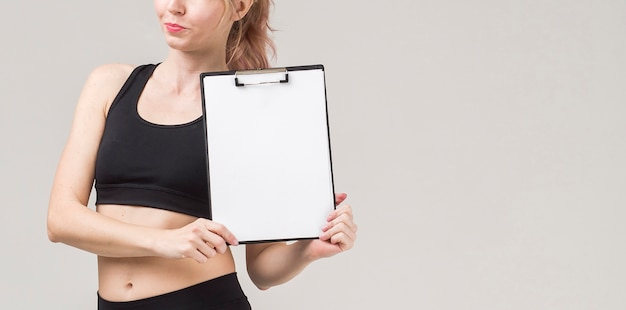 Front view of sporty woman holding notepad