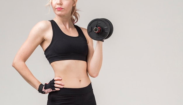 Front view of sporty woman lifting weight