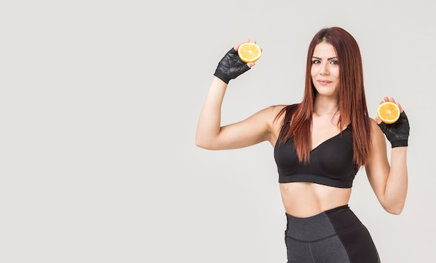 Front view of sporty woman posing with oranges