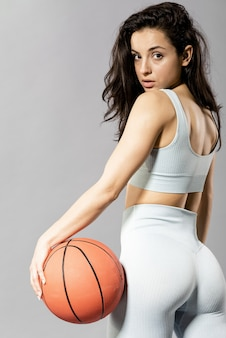 Front view of sporty woman with basketball ball