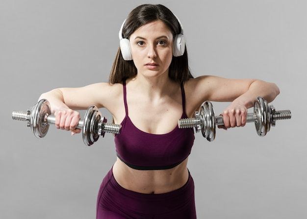 Front view of sporty woman with dumbbells