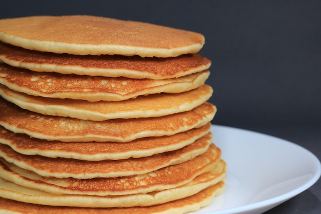 Front view of stack of homemade plain pancakes served on white plate on black background