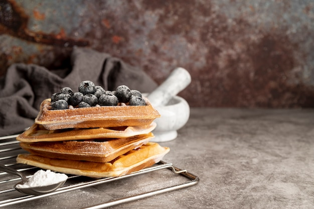 Front view of stack of waffles with blueberries and powdered sugar