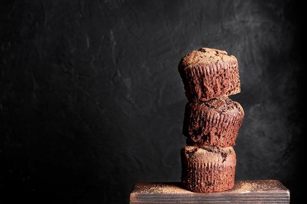 Vista frontale dei muffin al cioccolato impilati con lo spazio della copia