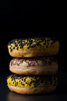 Front view of stacked doughnuts with different glazing and sprinkles