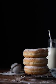Front view of stacked doughnuts with powdered sugar and milk bottle
