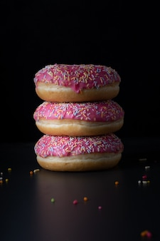 Front view of stacked glazed doughnuts with colorful sprinkles