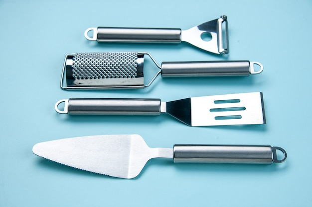 Front view of stainless kitchen tools lying side by side on soft blue wave background with free space