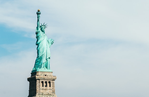 Front view of statue of liberty in new york with blue sky and copy space for text