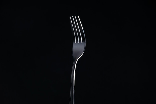 Front view steel fork on black surface free space