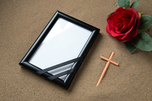 Front view of stick cross with red flower and picture frame on the sand