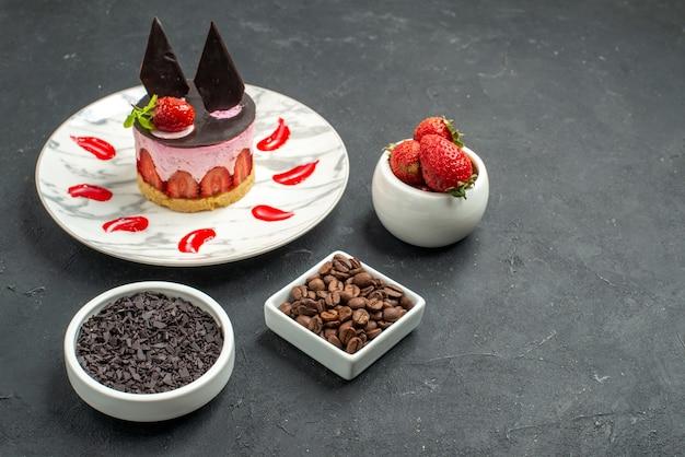 Вид спереди клубничный чизкейк на овальных тарелках с клубникой, шоколадом, кофейными семечками