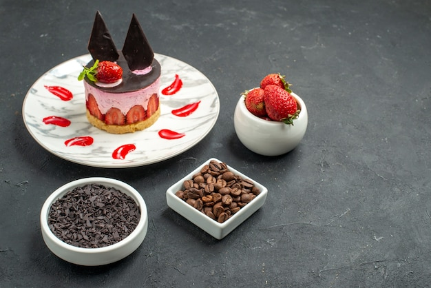 Front view strawberry cheesecake on oval plate bowls with strawberries chocolate coffee seeds