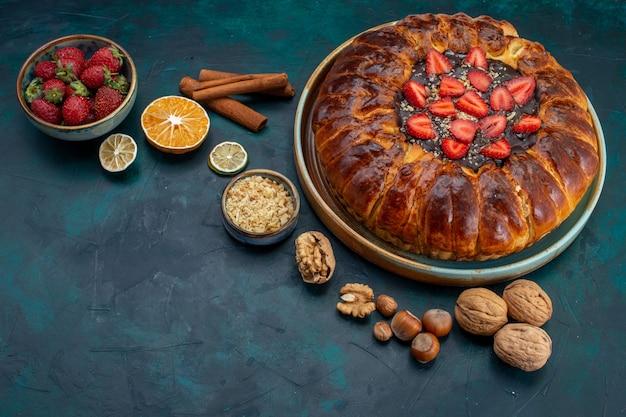 Vista frontale della torta di fragole con noci e cannella sulla scrivania blu scuro