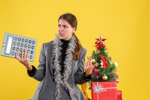 Front view stressed girl with calculator standing near xmas tree and gifts cocktail