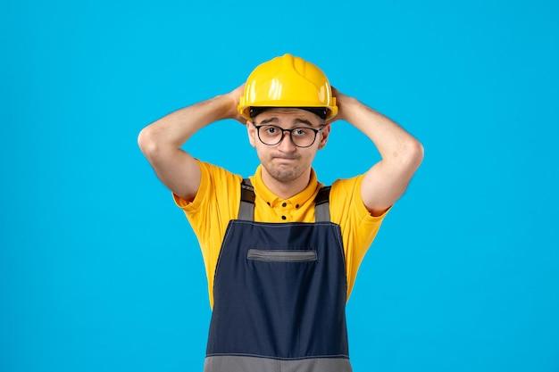 Vista frontale del lavoratore maschio sollecitato in uniforme e casco su un tuttofare lavoro pavimento blu