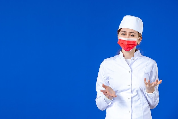 Front view of stressed young nurse in medical suit with red mask on blue