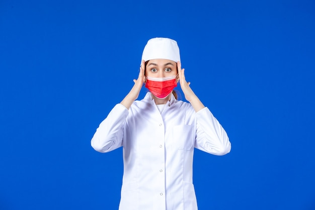Front view stressed young nurse in medical suit with red protective mask on blue wall
