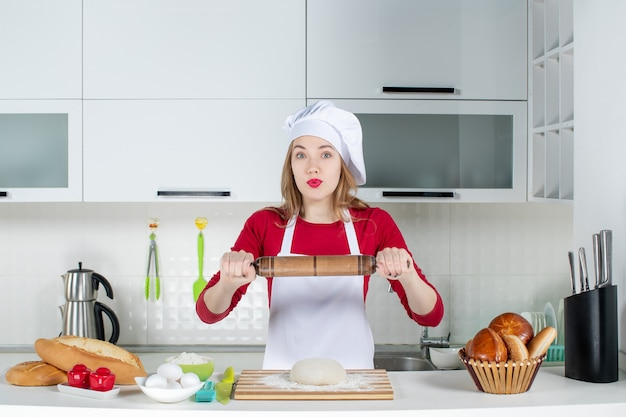 Front view strong female cook holding up rolling pin in the kitchen