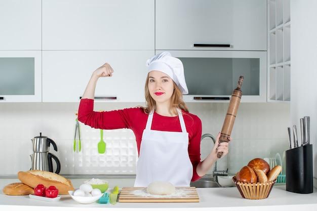 Vista frontale forte cuoca che mostra la sua forza tenendo il mattarello in cucina