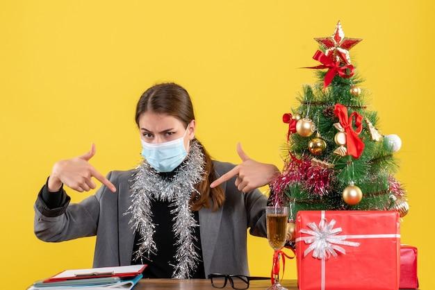 손가락 자신 크리스마스 트리와 선물 칵테일을 가리키는 테이블에 앉아 의료 마스크 전면보기 강한 어린 소녀